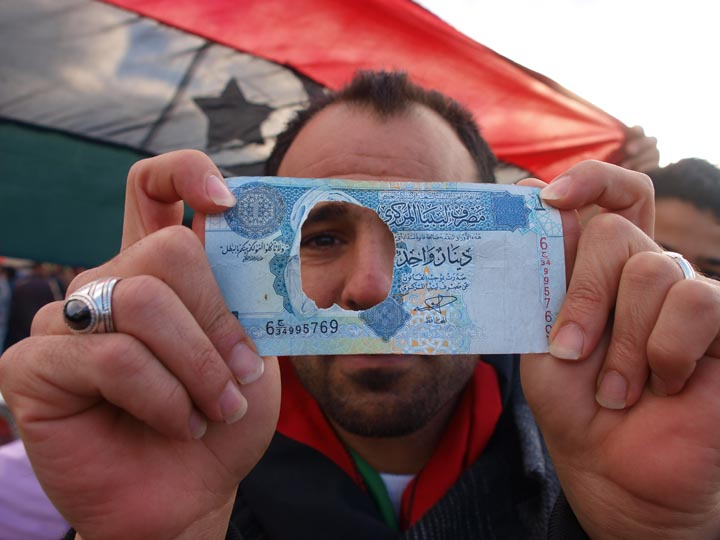A protestor marching on Benghazi's corniche on March 9, 2011 defaces as 1 dinar note featuring Muammar Qaddafi to shown his disdain for the Libyan dictator at the height of the Arab Spring movement. ©2012 Derek Henry Flood
