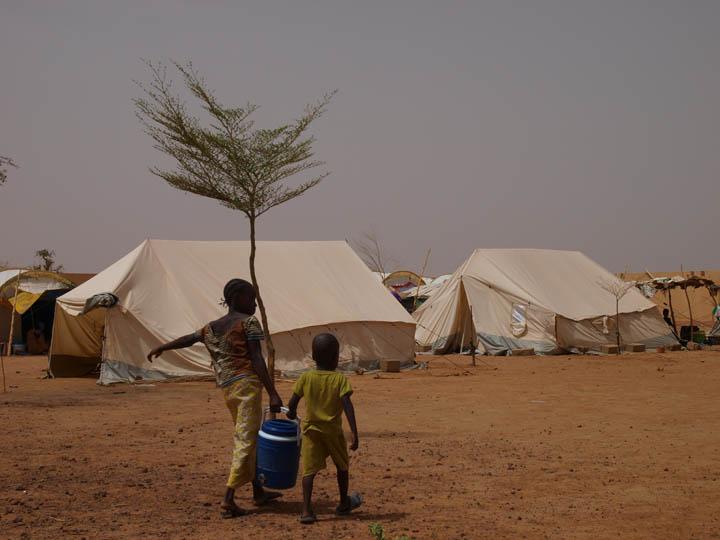 Children who fled the town of Gossi, Mali haul well drinking water back to their parents' tent at a camp for internally displaced people in Sévaré on June 4, 2012. ©2012 Derek Henry Flood