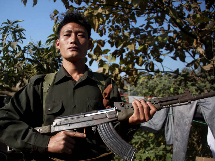 Young Kachin rebel A youthful KIA fighter clutches his rifle as a frame his forest portrait. ©2013 Raymond Pagnucco
