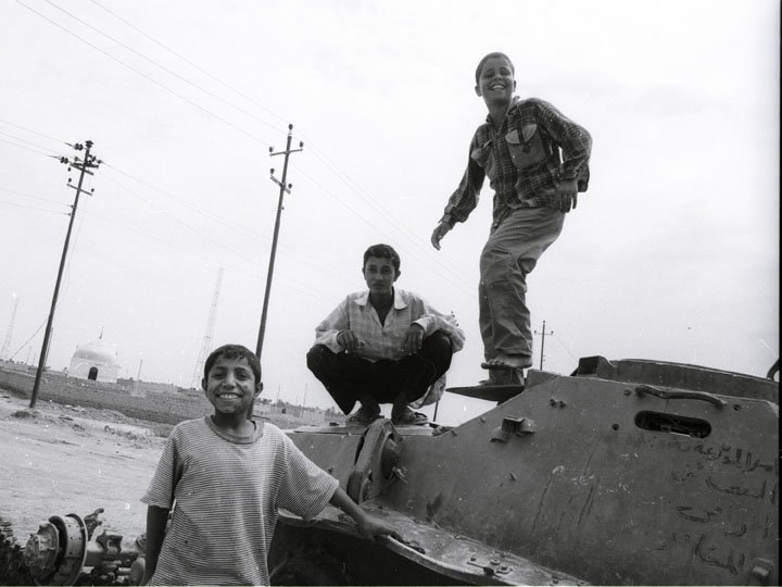 iraqi boys play atop a destroyed Soviet BTR armored personnel carrier on the road between Nasiriyah and Najaf. ©2003 Derek Henry Flood