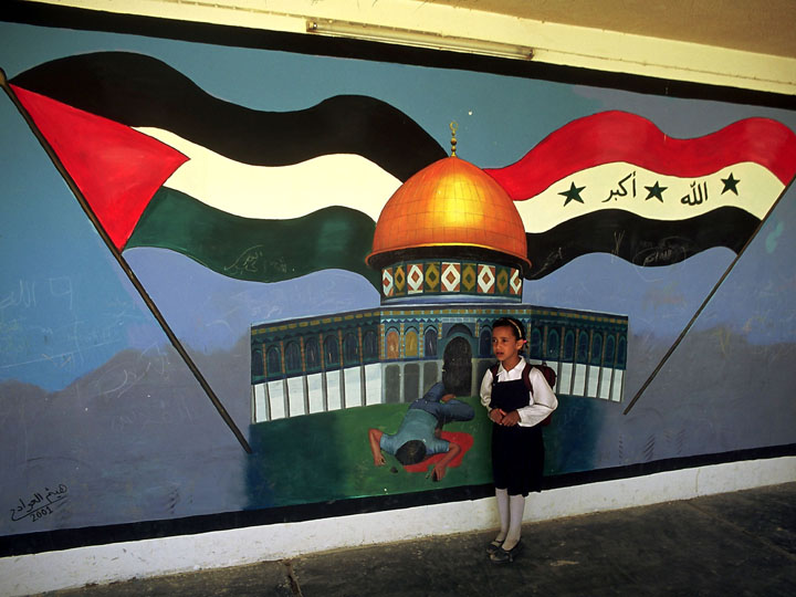 A young Shia girl returns to school after the American invasion of her country. Behind her is a mural of Muhammed Al-Dura, a young  boy killed during the second intifada in Palestine. ©2003 Derek Henry Flood