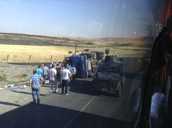 A Turkish Jandarma (Gendarmerie) hard car and a host of lookie loos inspect a jackknifed Turkish big rig that was transporting bottled water to Iraq. ©2013 Derek Henry Flood