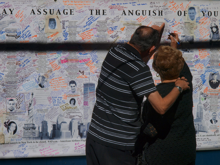 Relatives of victims sign a Ground Zero tribute wall outside the annual memorial ceremony on the ninth anniversary of the 9/11 terror attacks in lower Manhattan. ©2010 Derek Henry Flood