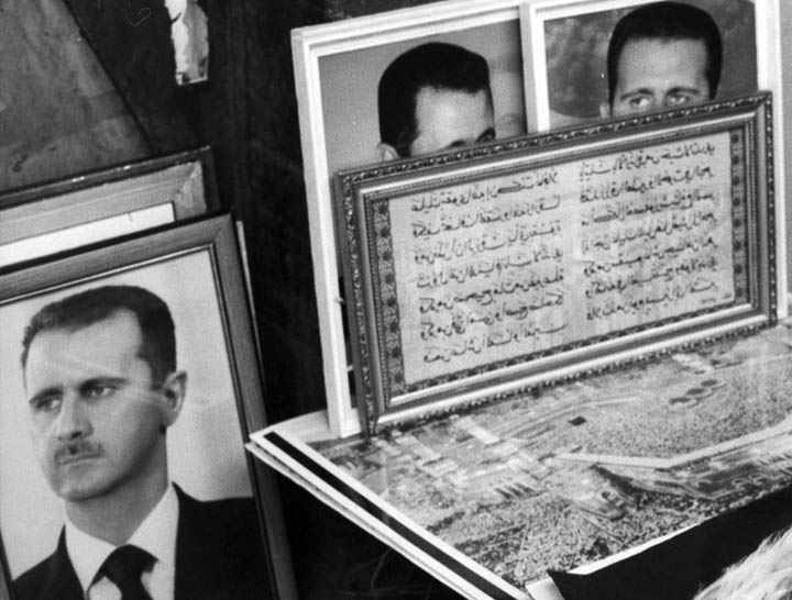 Portraits of Ba'athist leader Bashar al-Assad gazing off in different directions at a market in Damascus two years after he succeeded his father. ©2002 Derek Henry Flood