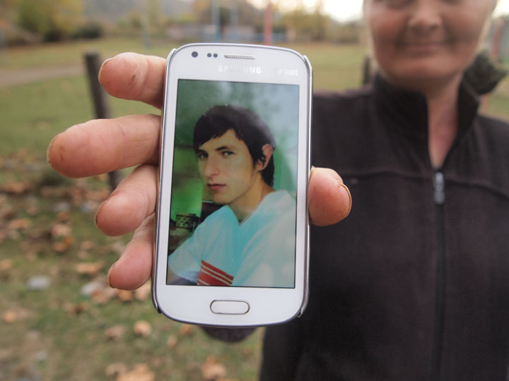 Rustam Gelayev's aunt holds up a smartphone image of her late nephew who, like Murad, died in northern Syria in August 2012. ©2013 Derek Henry Flood