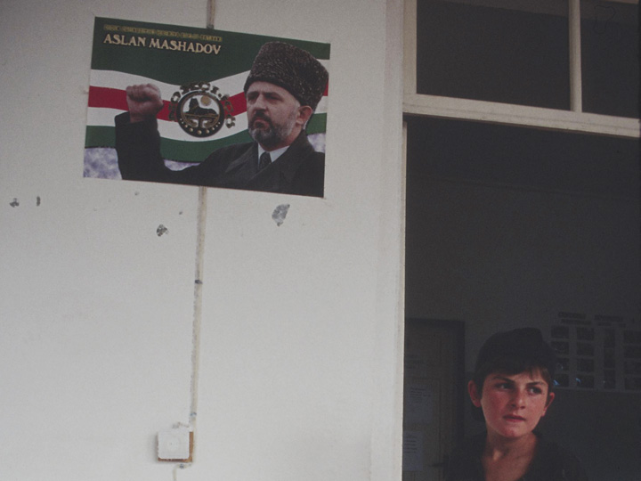 At the school building in Duisi, then being run by a Norwegian NGO, a Chechen refugee boy stands beneath a Turkish-made poster of Aslan Maskhadov, the emblematic leader of Chechen national liberation movement. ©2002 Derek Henry Flood