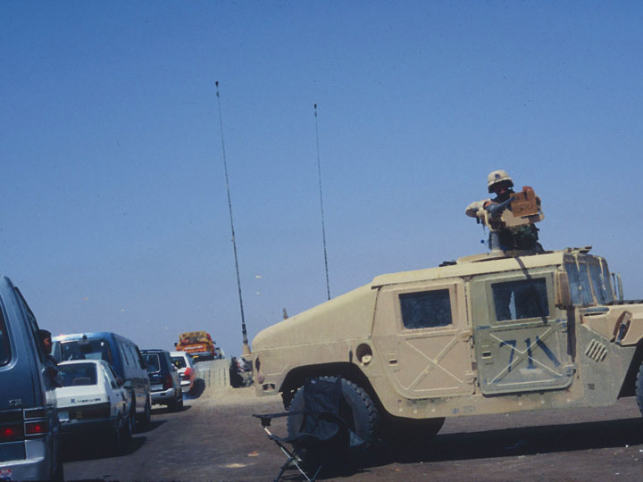 "An American Humvee gunner holds a makeshift sign that reads ""Go"" in English and then Arabic at the entrance to a bridge over that Tigris River that has been partially destroyed by American munitions. ©2003 Derek Henry Flood"