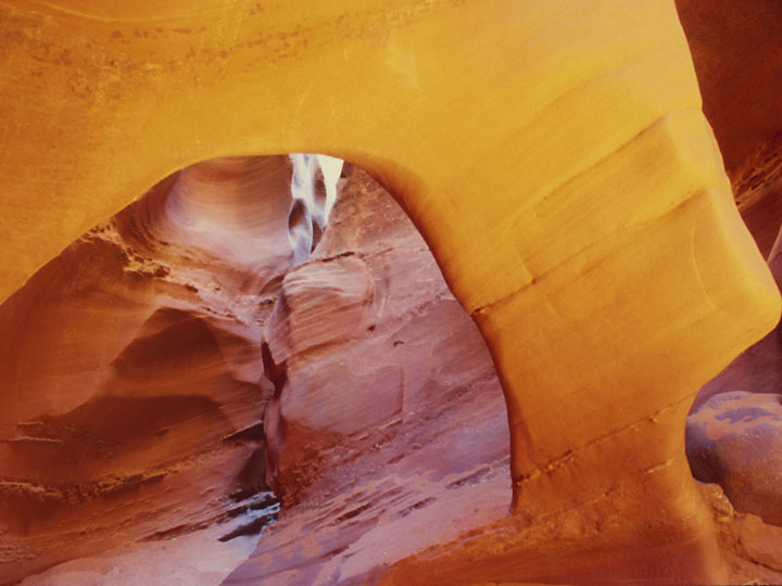 An arch inside Spooky Gulch being light up by reflected sunlight beaming down from the crevice above. ©1999 Derek Henry Flood