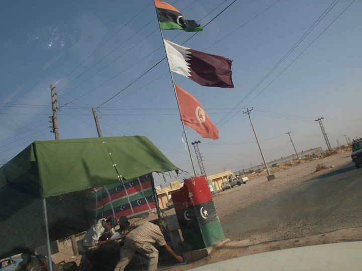 To relative safety. After being nearly shot by a regime sniper nest in Qwaleesh my agile driver roared our Hi-Lux back to a friendly checkpoint hoisting Qatari and Tunisian flags. ©2011 Derek Henry Flood