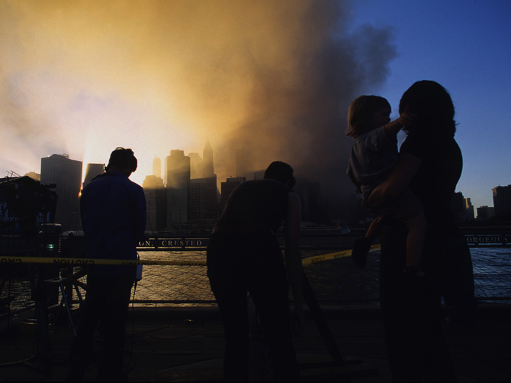 A mother holds her daughter while gazing at the plume in the aftermath of the destruction of the World Trade Center on 9/11. To their left TV crews prepare to broadcast. This never before seen image was made adjacent the River Cafe on Brooklyn's DUMBO waterfront at approximately 8pm after the suicide attacks killed nearly 3000. ©2001 Derek Henry Floo