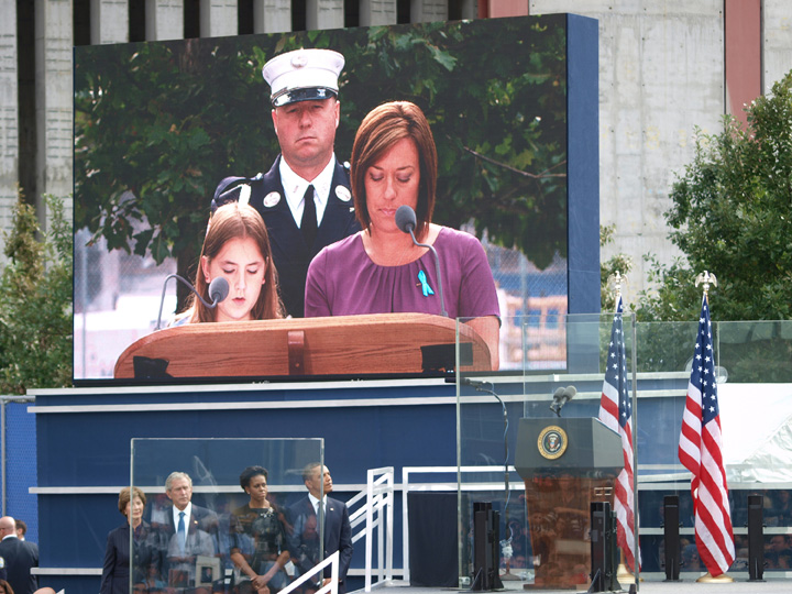 A giant projection outside the WTC memorial shows family members reciting the names of the nearly 3000 killed on 9/11. President Barack Obama Michelle Obama George W. Bush and Laura Bush look on as families of the victims speak from the podium. ©2011 Derek Henry Floo