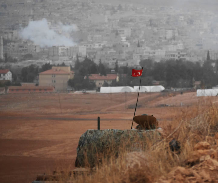 A Turkish tank hugs a hillside in Mursitpinar as street fighting rages across the plain in Kobane. ©2014 Derek Henry Flood