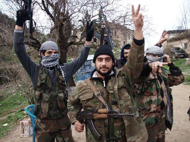 Syrian fighters in Idlib mimicking the hand gesture of Libyan revolutionaries who had overthrown Qaddafi the previous year with the help of Western air power. ©2011 Derek Henry Flood
