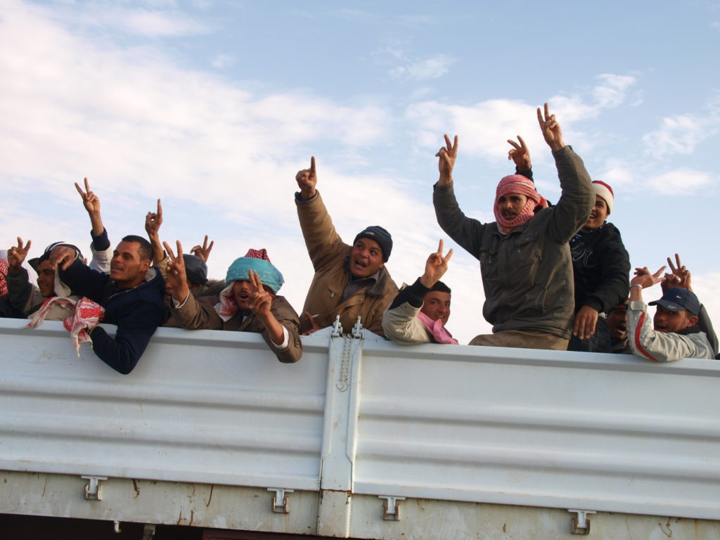 Egyptian migrant workers gleefully fleeing the frontline in Brega, Libya on March 2, 2011. ©2011 Derek Henry Flood