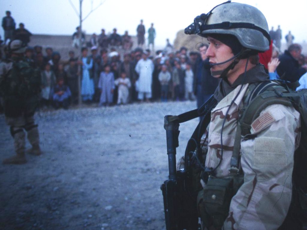An American soldiers stands at dusk among a crowd of IDPs and Jamiat supporters on a USAID escort mission. ©2001 Derek henry Flood