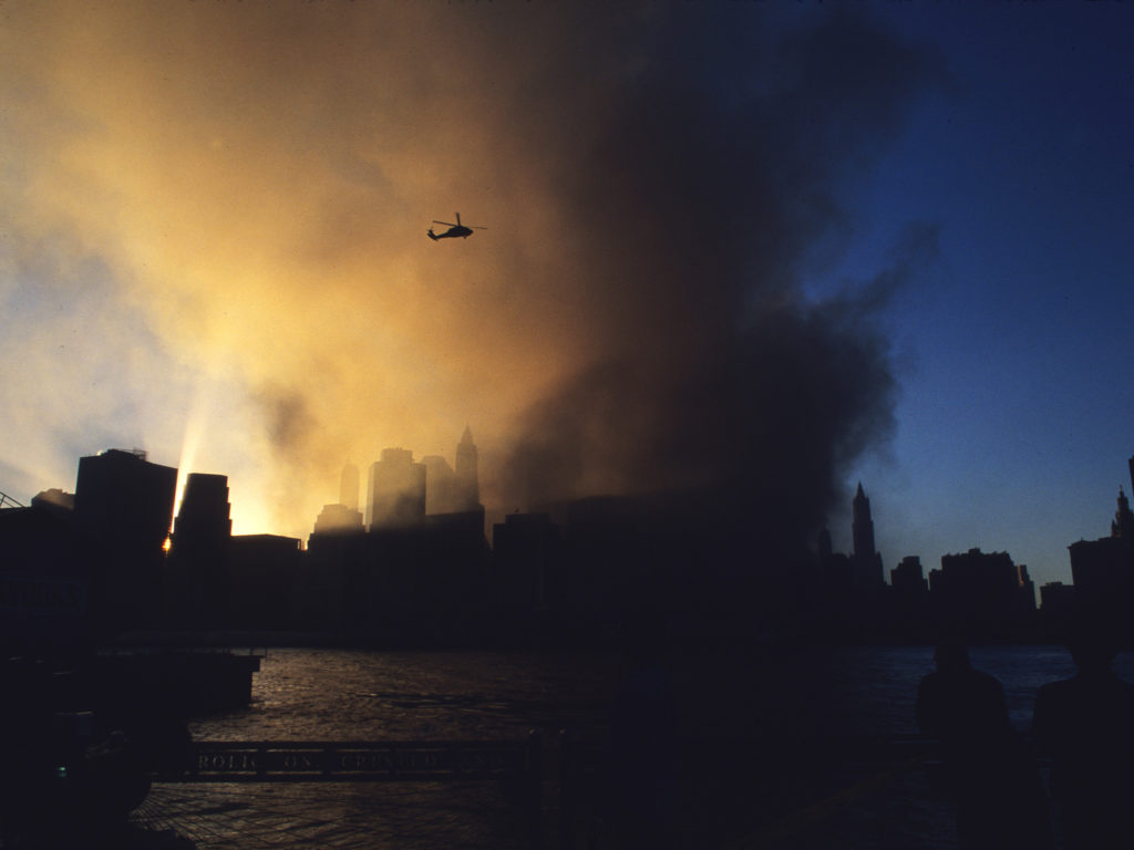 A Blackhawk helicopter flys above the plume surveying the destruction of the World Trade Center on 9/11. This never before seen image was made adjacent the River Cafe on Brooklyn's DUMBO waterfront at approximately 8pm after the suicide attacks killed nearly 3000. ©2001 Derek Henry Flood
