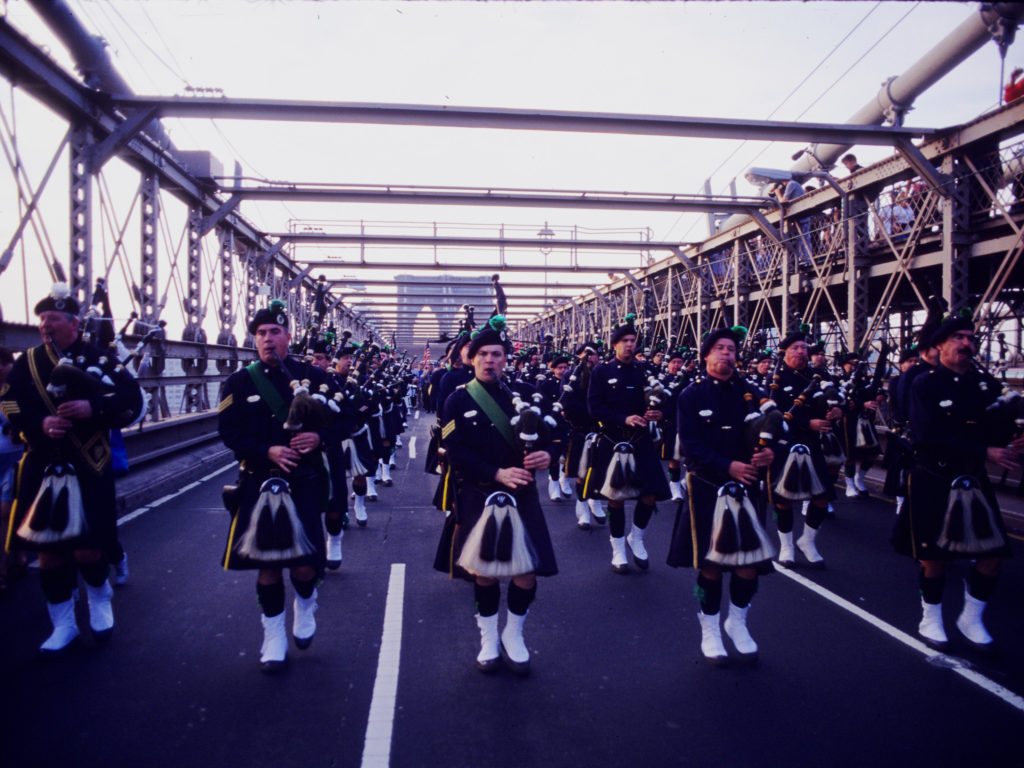 The New York City police department bagpipe troupe marches over the Brooklyn Bridge at dawn on the one year anniversary of 9/11. ©2002 Derek Henry Flood