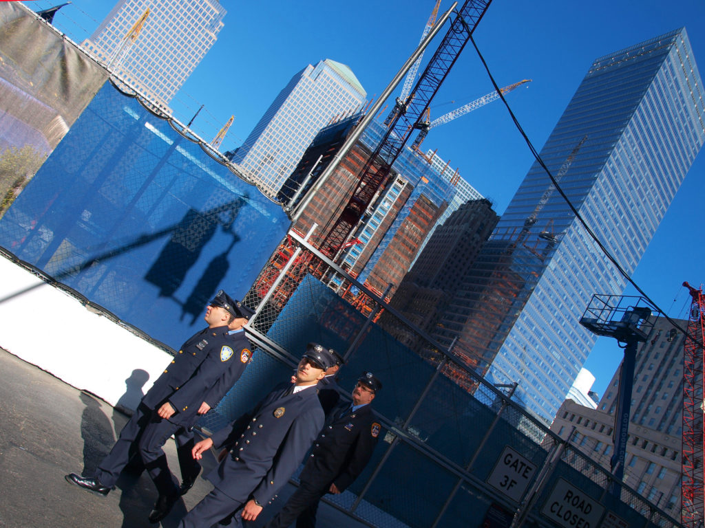 A group of New York City firefighters pass by a Ground Zero outside the annual memorial ceremony on the ninth anniversary of the 9/11 terror attacks in lower Manhattan with the construction of a new tower finally begginning to arise from the void in the background. ©2010 Derek Henry Flood