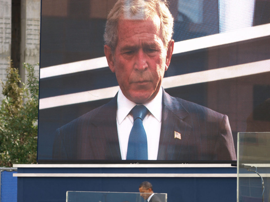 President Barack Obama exits the stage after giving an impassioned speech for the families of victims at the ceremony in Lower Manhattan to mark the 10th anniversary of 9/11. A sorrowful George W. Bush stands on the overhead screen. While the Obamas remained composed throughout the ceremony the Bush's displayed visible signs of emotion as the events of 9/11 were collectively remembered. ©2011 Derek Henry Flood