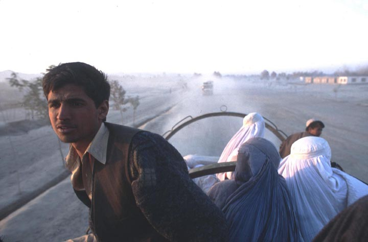 In what the US Army refers to as a 'jingle truck,' a group of IDPs (internally displaced persons) ride atop sacks of wheat donated by NGOs during the Afghan civil war. ©2001 Derek Henry Flood